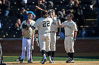 Will Craig (22) of the Wake Forest Demon Deacons is greeted at home plate by teammates Joey Rodriguez (right) and Kevin Conway (7) after hitting a home run against the Richmond Spiders at David F. Couch Ballpark on March 6, 2016 in Winston-Salem, North Carolina.  The Demon Deacons defeated the Spiders 17-4.  (Brian Westerholt/Four Seam Images)