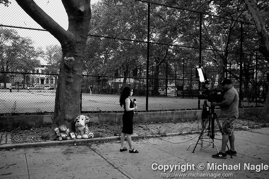 BROOKLYN, NY — JULY 13, 2021:  Hannah Kliger, News 12 Brooklyn reporter, left, and Christian Braxton, News 12 Brooklyn news photographer, right, report in front of a memorial for 1 year-old Davell Gardner, Jr., who was shot while sitting in his stroller at a barbecue a year ago today, at Raymond Bush Playground in Brooklyn, NY on July 13, 2021. Two suspects were charged in May, in what investigators believe to be part of a feud between rival gangs. Photograph by Michael Nagle