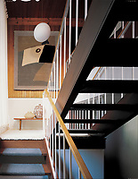 A double flight open staircase with a simple hand rail