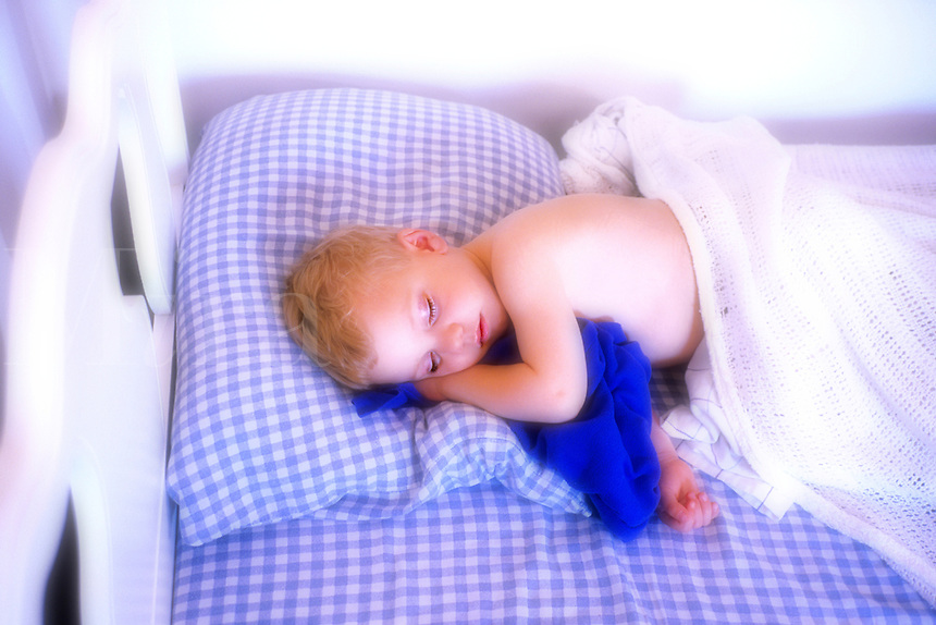 Child sleeping in white bed with blue check sheets, soft focus in one channel