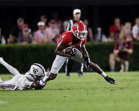 ATHENS, GA - SEPTEMBER 18: Adonai Mitchell #5 evades a tackle by Cam Smith #9 during a game between South Carolina Gamecocks and Georgia Bulldogs at Sanford Stadium on September 18, 2021 in Athens, Georgia.
