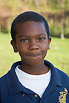 Black male second grade student  with short hair in school uniform looks at camera closeup outdoors.