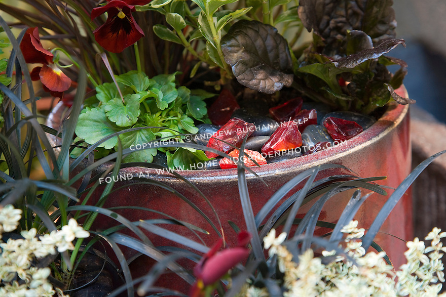 A mix of recycled, tumbled red glass and black stones echo both the pots, and the flowers and foliage of chrysanthemums, black mondo grass, deep red pansies, variegated thyme, black-leaved ajuga, and others.