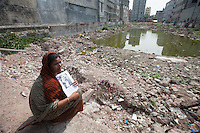 Relatives of victims killed in the collapse of Rana Plaza sits in front of the collapse site with the picture of her daughter during the second anniversary of the building collapse in Savar, near Dhaka, Bangladesh