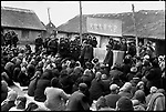 """Under a banner that reads """"Struggle against the enemies rally,"""" Zhang Diange is denounced as a rich peasant by members of the Nansheng production brigade and made to bow his head for hours. Ashihe commune, Acheng county, Heilongjiang Province, 25 March 1965"""