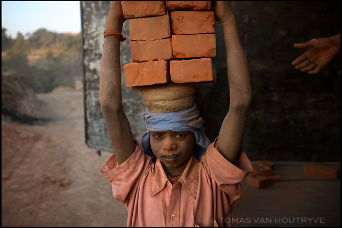 A boy carries finnished bricks on his head to be loaded in a truck at a brick factory near Bhaktapur, Nepal on 27 December, 2005. Brick factories throughout South Asia employ some of the region's poorest labourers. In Nepal, the workers are usually  members of the lowest castes, and often children.<br />