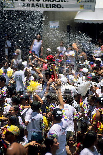 Salvador, Brazil. Crowd of people enjoying a refreshing shower of water from a hose during carnival.