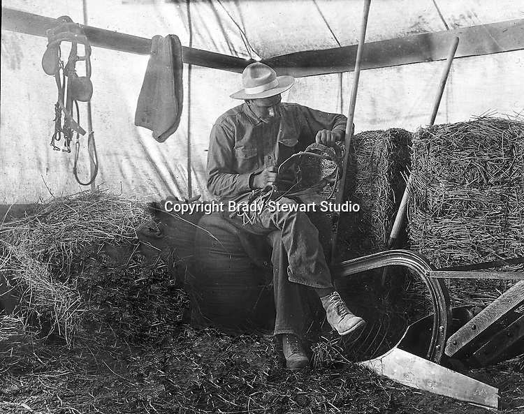 Products: Horse Harness, saw, plow and pitchfork <br /> <br /> Jerome ID: Repairing equipment on the farm.   Brady Stewart and three friends went to Idaho on a lark from 1909 thru early 1912. As part of the Mondell Homestead Act, they received a land grant of 160 acres north of the Snake River. The homesteaders set up a tent next to the farmhouse to keep feed, hay, and equipment while the main house was under repair.  For 2 ½  years, Brady Stewart photographed the adventures of farming along with the spectacular landscapes.
