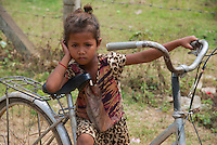 Young girl and her bike on Silk Island outside Phnom Penh, Cambodia. Home of the Traditional Khmer Silk production