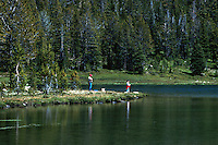 Father and son fishing on a lake.