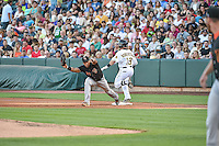 Jon Singleton (21) of the Fresno Grizzlies makes the stretch to beat a running Daniel Robertson (13) of the Salt Lake Bees in Pacific Coast League action at Smith's Ballpark on June 13, 2015 in Salt Lake City, Utah.  (Stephen Smith/Four Seam Images)