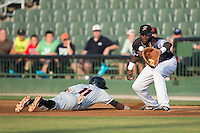 KJ Woods (24) of the Kannapolis Intimidators waits for a pick-off throw as Cedric Mullins (11) of the Delmarva Shorebirds dives back into first base at Kannapolis Intimidators Stadium on June 25, 2016 in Kannapolis, North Carolina.  The Intimidators defeated the Shorebirds 2-1.  (Brian Westerholt/Four Seam Images)