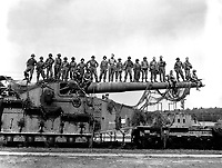 Mammoth 274-mm railroad gun Captured in the U.S. Seventh Army advance near Rentwertshausen easily holds these 22 men lined up on the barrel.  Although of an 1887 French design, the gun packs a powerful wallop.  April 10, 1945.  T5c. Pat. W. Kohl. (Army)<br /> NARA FILE #:  111-SC-203308<br /> WAR & CONFLICT BOOK #:  1098