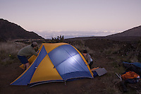 A couple setting up their tent in Haleakala Crater at dusk