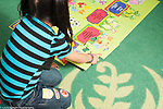 Education preschool 3-4 year olds girl finishing floor puzzle showing numbers
