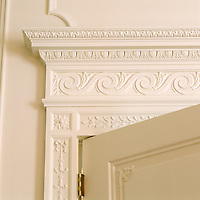 A detail illustrating the white painted neo-classical mouldings around an antique door