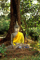 Thailand.  Stucco figure of Buddha at the foot of a tree.  Wat Prathat Chom Kitty, Chiang Saen, ancient Thai capital on the Mekon River in the north of the country.