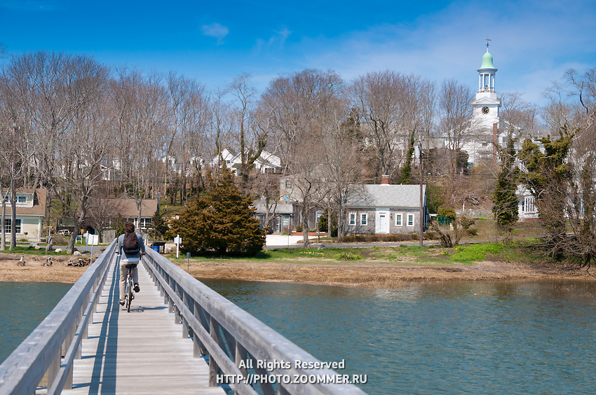 Man riding a bike over Uncle Tim's Bridge In Wellfleet with church behind, Cape Cod