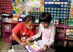 Education Elementary New Jersey public school grade 1 math activity boy and girl using ruler to measure different items in the classroom
