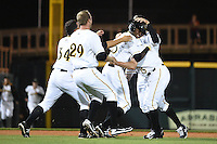 Bradenton Marauders outfielder Raul Fortunato (35) is mobbed by teammates including Jhondaniel Medina (34), Jordan Steranka (29), Jonathan Schwind (13) after the game winning hit during a game against the Palm Beach Cardinals on April 8, 2014 at McKechnie Field in Bradenton, Florida.  Bradenton defeated Palm Beach 4-3.  (Mike Janes/Four Seam Images)