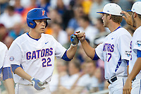 Florida Gators designated hitter JJ Schwarz (22) is greeted by teammate Shaun Anderson (37) after scoring against the Miami Hurricanes in the NCAA College World Series on June 13, 2015 at TD Ameritrade Park in Omaha, Nebraska. Florida defeated Miami 15-3. (Andrew Woolley/Four Seam Images)