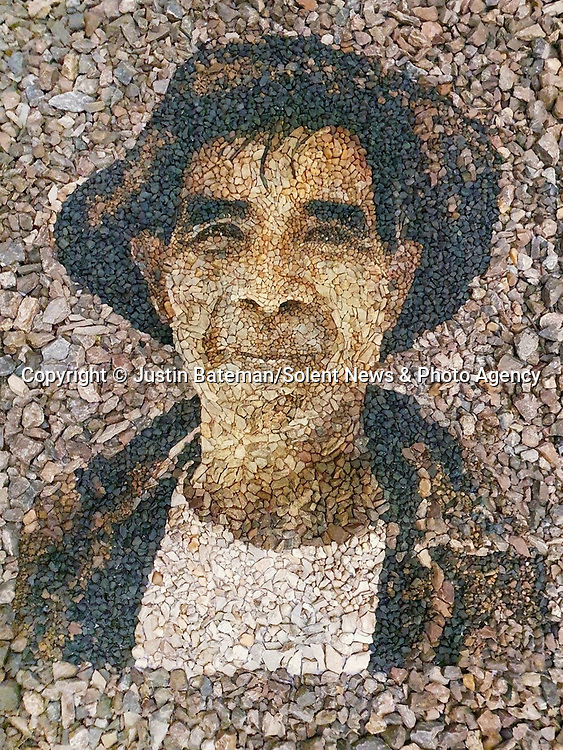 Pictured: 'Cattle Herder'. Using found stones. The farmer who works the land, made of the land, upon the land he works. Chiang Mai, Thailand.  The Farmers name is unknown. He preferred to remain anonymous. <br /> <br /> A British artist stuck in Thailand has spent his time constructing masterpieces from pebbles for locals to enjoy.  Justin Bateman had only planned on staying in Chiang Mai for a week - but has remained there now for nearly ten months after the pandemic struck. <br /> <br /> His pebble portraits include The Queen, Spanish painter Pablo Picasso, Michelangelo's David and a local farmer - who was bemused by his portrait.   Mr Bateman, from Portsmouth, Hants, was staying in Bali when he travelled to Chiang Mai, in Thailand, to visit some friends.   SEE OUR COPY FOR DETAILS.<br /> <br /> Please byline: Justin Bateman/Solent News<br /> <br /> © Justin Bateman/Solent News & Photo Agency<br /> UK +44 (0) 2380 458800