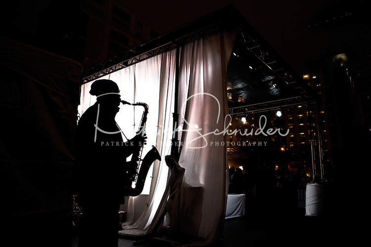 A silhouetted saxophone player warms up back stage during First Night Charlotte 2010. The family-friendly public event (no alcohol allowed) is an annual cultural New Year's Eve celebration held in downtown / uptown / Charlotte center city. Charlotte First Night - An Imagination Celebration brought together artists, musicians, dancers and more from across the country. The New Year's event is organized by Charlotte Center City Partners, which facilitates and promotes the economic and cultural development of this North Carolina urban core.