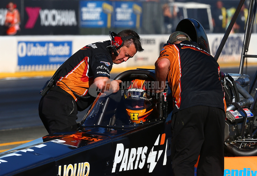 Jul. 25, 2014; Sonoma, CA, USA; Crew members push NHRA top fuel driver Clay Millican back after his burnout during qualifying for the Sonoma Nationals at Sonoma Raceway. Mandatory Credit: Mark J. Rebilas-