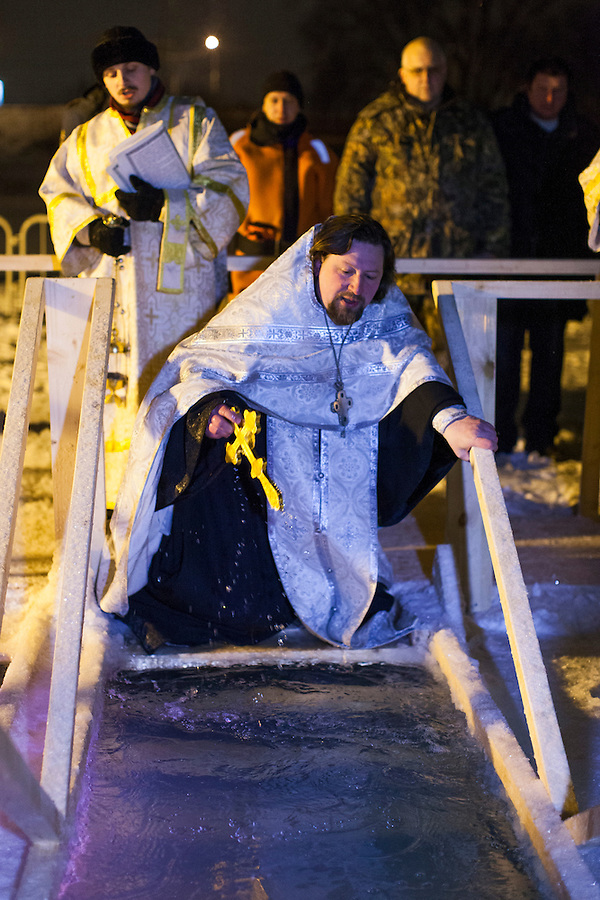 Moscow, Russia, 18/01/2014.<br /> A priest dips a cross in the water as Orthodox Christian believers celebrate Epiphany at a lake in southern Moscow. Priests blessed the waters and followers baptised themselves by total immersion in the freezing lake in temperatures of minus 18C