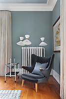 A 1950s chair, floor lamp and metal trolley create a smart retro arrangement in one corner of the living room