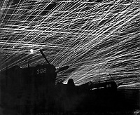 """Japanese night raiders are greeted with a lacework of anti-aircraft fire by the Marine defenders of Yontan airfield, on Okinawa.  In the foreground are Marine Corsair fighter planes of the """"Hell's Belles' squadron.  1945.  T.Sgt. Chorlest.  (Marine Corps)<br /> Exact Date Shot Unknown<br /> NARA FILE #:  127-G-118775<br /> WAR & CONFLICT BOOK #:  1235"""