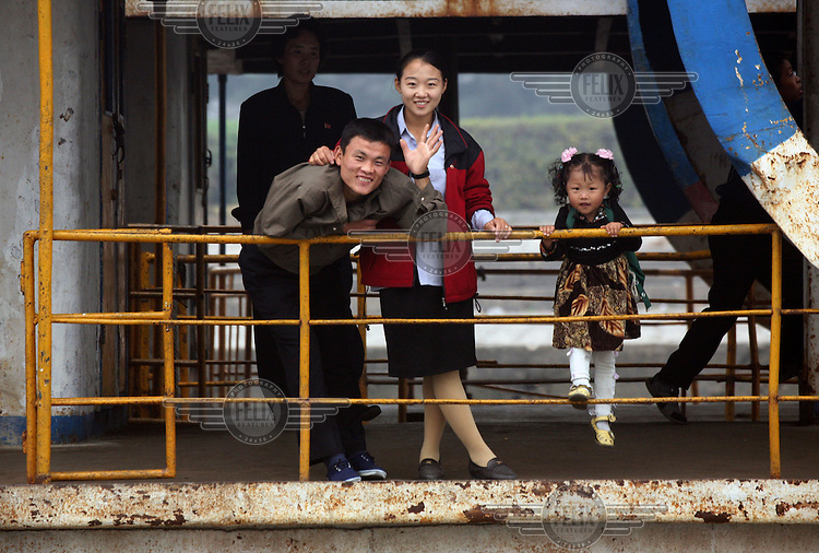 A North Korean family wave to a Chinese tourist boat on the Amrok (Yalu) River, which marks the border between North Korea and China.