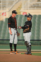 Delmarva Shorebirds catcher Yermin Mercedes (8) has a chat with relief pitcher Garrett Cortright (10) as he enters the game against the Kannapolis Intimidators at CMC-Northeast Stadium on June 7, 2015 in Kannapolis, North Carolina.  The Shorebirds defeated the Intimidators 9-1.  (Brian Westerholt/Four Seam Images)