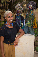 Sara Maurin Kane Standing Next to Mami Watas, Artistic Creations of Sylvette Maurin.  Goree Island, Dakar, Senegal.  In West African mythology, mami watas are Mythological Guardians of the Sea. Model and Property released.