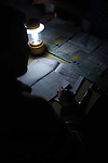 KIRKUK, IRAQ:  A man counts votes by lamplight after the electricity goes out at a polling station...On March 7th, 2010 Iraq held national parliamentary elections...Photo by Hawre Khalid/Metrography