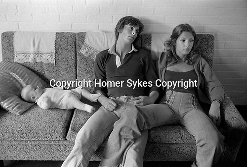 1970s fashionable young middle class couple in jeans, casual clothes, in love legs touching, chilling out, in a friends home.1977 Milton Keynes Buckinghamshire 1970s UK