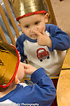 toddler boy 18 months old recognizing self looking at reflection in mirror, touching nose with finger