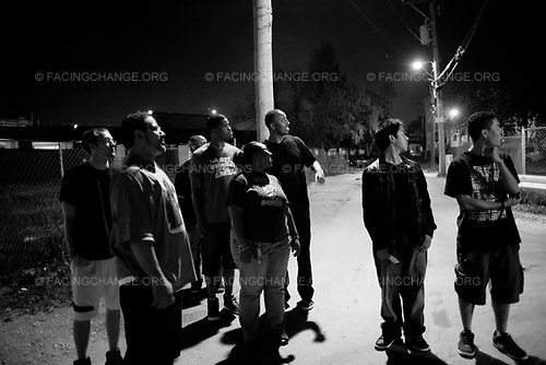 Chicago,Illinois<br /> USA<br /> June 2010<br /> <br /> Pastor Phil Jackson walks the streets with his young church members who volunteer to talk to teens and young men on the west side of Chicago.  Pastor Jackson's mission is to keep the gang violence down while they are hanging out on street corners. Church members and churchgoers  worship at the house. The house is a church with a different twist.  They play hip-hop music and praise the Lord. After church on Saturday's in the summers Pastor Phil Jackson and other young church goers walked the streets of the Westside of Chicago. The Westside is one of the most gan infested neighborhoods in Chicago. Pastor Jackson talks to people on the corner and helps to find jobs for teens and young men and woman in his community.