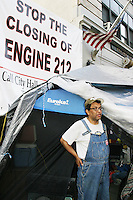 A protester stands outside of his tent in front of Fire Engine 212 in Brooklyn, NY on August 21, 2003.<br /> <br /> Mayor Bloomberg's administration identified this firehouse, and seven others in NYC, as underused and ordered their closing to save the city up to 11 million dollars.  To protest its mandated closing, a group of residents turned into dissidents and maintained a 24 hour camp in front of the firehouse to prevent it from being shut down.