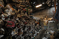 Migrant worker sorts through waste in a trash town in China. Lian Jiao town near Nanhai in China's Guangdong Province is a heavily polluted township that recycles waste plastic, much of which is brought from European countries..30 Aug 2006