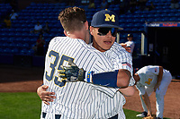 Michigan Wolverines Brock Keener (35) hugs Hector Gutierrez (24) before a game against Army West Point on February 18, 2018 at Tradition Field in St. Lucie, Florida.  Michigan defeated Army 7-3.  (Mike Janes/Four Seam Images)