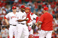 Jerome Williams #57 of the Los Angeles Angels hands the ball to Angels Manager Mike Scioscia #14 after being taken out of a game against the St. Louis Cardinals at Angel Stadium on July 3, 2013 in Anaheim, California. (Larry Goren/Four Seam Images)