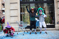 On the second day of celebrations, masked participants in Fasnacht pose for the camera as two children pick through a bag of blue confetti in the old town of Basel, Switzerland. Feb. 24, 2015.