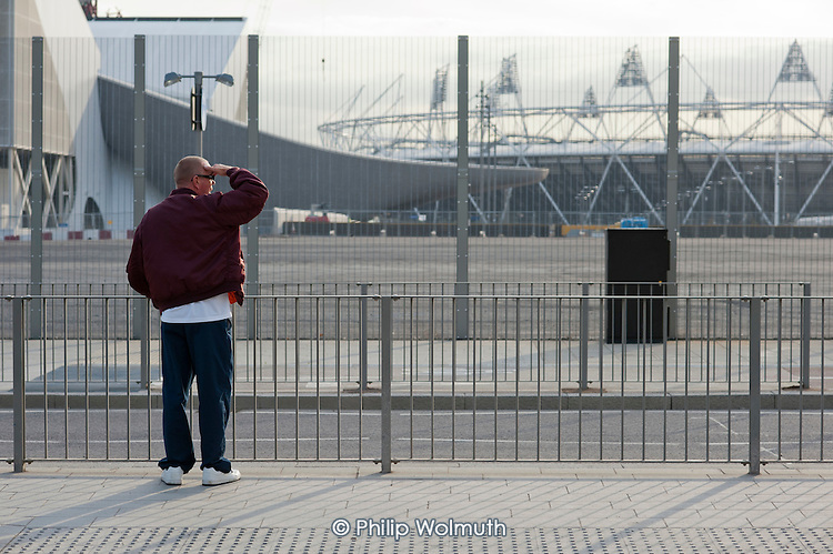 A local resident views the Olympic stadium from Westfield Stratford City, the largest urban shopping centre in Europe, will be the gateway to the London 2012 Olympic Park. 2,000 of the 10,000 permanent jobs at the new retail complex have gone to the local unemployed.