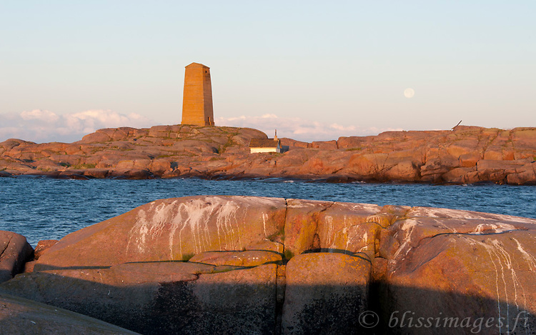 Nature abounds at the skerries of Segelskär and leaves its myriad markings. The full moon lingers on at daybreak in the Gulf of Finland.