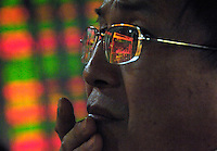 Chinese investor watches stock index in a stock exchange of Beijing. Chinese share prices broke through the psychologically important 4000-mark for the first time ever last week and dealers said the sustained Chinese advance is being driven by massive inflows of fresh funds as smaller investors take their money out of low-return bank deposits and punt on stocks..15 May 2007