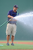 Head groundskeeper Greg Burgess waters down the infield before a game between the Charleston RiverDogs and the Greenville Drive on Thursday, August 21, 2014, at Fluor Field at the West End in Greenville, South Carolina. (Tom Priddy/Four Seam Images)