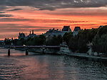 The sun sets behind the Louvre in an evening view of the Seine from the Pont Neuf.