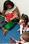 Education preschool first days of school sad boy held by female teacher as classmates look on