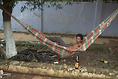 Xapuri, Acre, Brazil. Homeless young migrant man lying in a hammock slung between two trees at the side of the street with empty cachaca sugar cane alcohol bottles and a sardine tin.